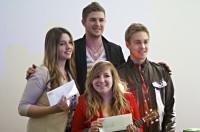 A group of teenagers standing and holding up envelopes
